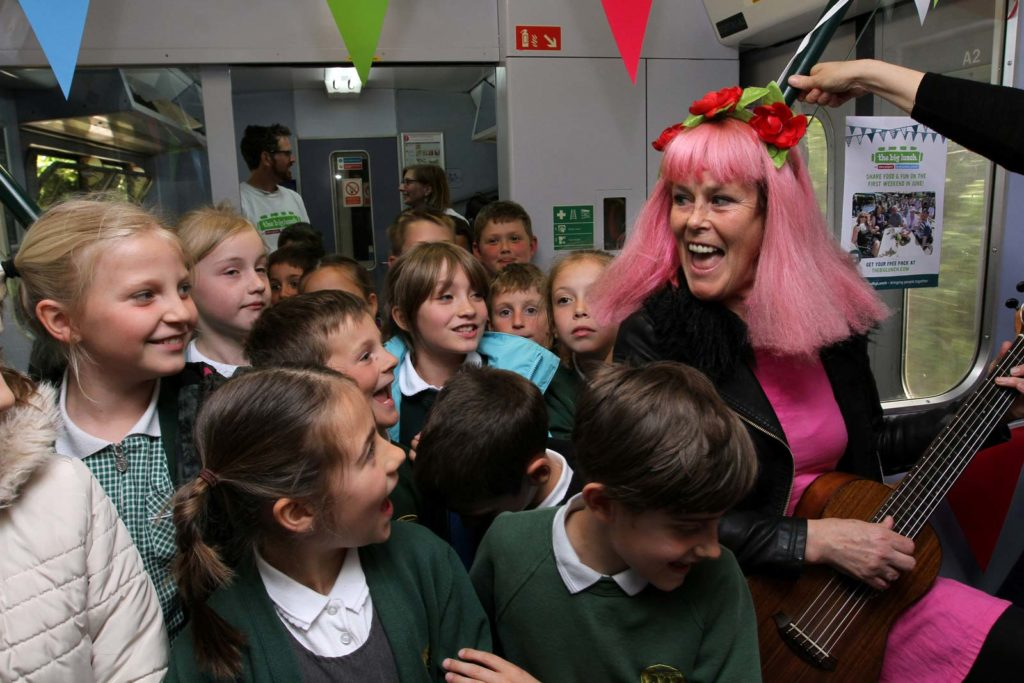 Poet Sally Crabtree sings with local school children on the Creativitea train