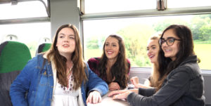 Four students look out of the train window on the Tarka Line (screenshot from video)